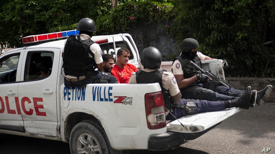 Police take two detainees to the police station of Petion Ville, Port-au-Prince, Haiti, July 8, 2021. According to Police Chief Leon Charles, the two detainees are suspects in the assassination of Haitian President Jovenel Moïse.
