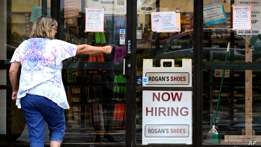 FILE - A hiring sign is displayed outside a retail store in Buffalo Grove, Illinois, June 24, 2021.