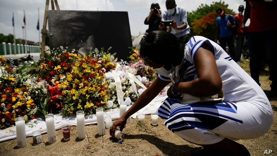 A woman lights a candle at a memorial outside the Presidential Palace in memory of slain President Jovenel Moise, in Port-au-Prince, Haiti, July 14, 2021, a week after Moise was assassinated at his home.