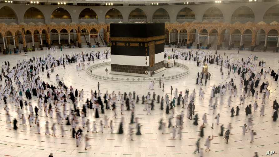 Muslim pilgrims circumambulate the Kaaba, the cubic building at the Grand Mosque, as they wear masks and keep social distancing, a day before the annual hajj pilgrimage in Mecca, Saudi Arabia, July 17, 2021.