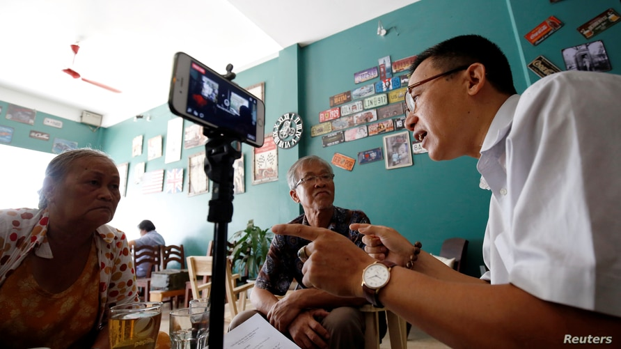 FILE - Journalist and rights activist Le Van Dung (R) conducts a livestream on Facebook in a coffee shop in Hanoi, Vietnam, May 15, 2018.