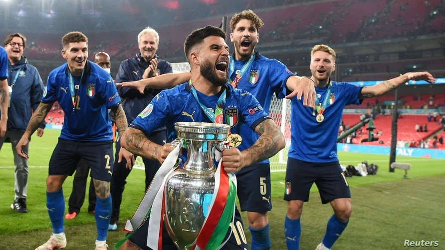 Italy's Lorenzo Insigne, holding a trophy, celebrates with teammates after they win the Euro 2020 soccer championship final match against England, at Wembley stadium, London, July 11, 2021.
