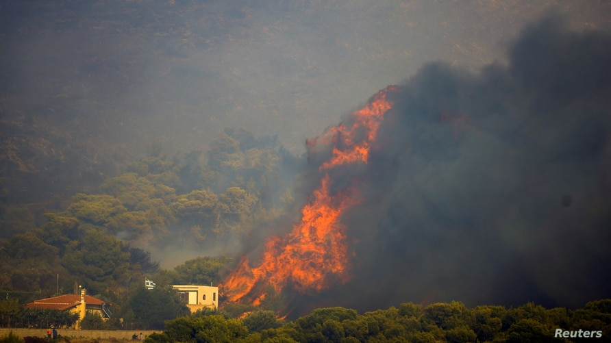 Flames rise next to a house as a wildfire burns in the village of Sinterina, Greece, Aug. 16, 2021.
