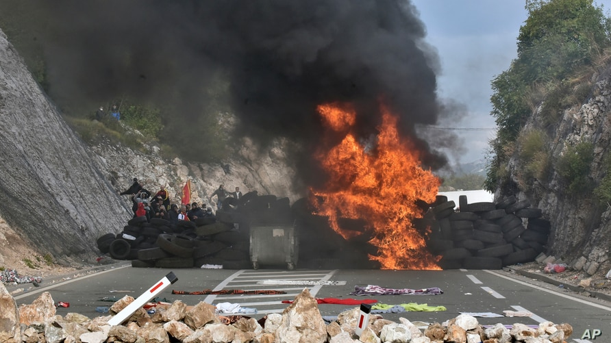 Protesters set fire to car tires at one of the blockades near Cetinje, Montenegro, Sept. 5, 2021.