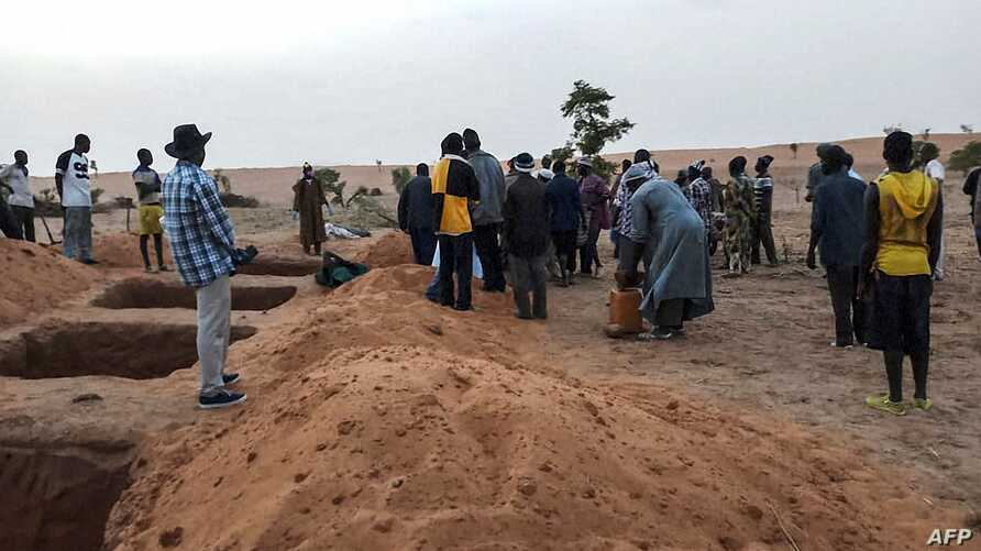 Officials and residents stand near freshly dug graves on June 11, 2019 in the Dogon village of Sobane-Kou, near Sangha, after an attack that killed over 100 ethnic Dogon on June 9, 2019 evening.