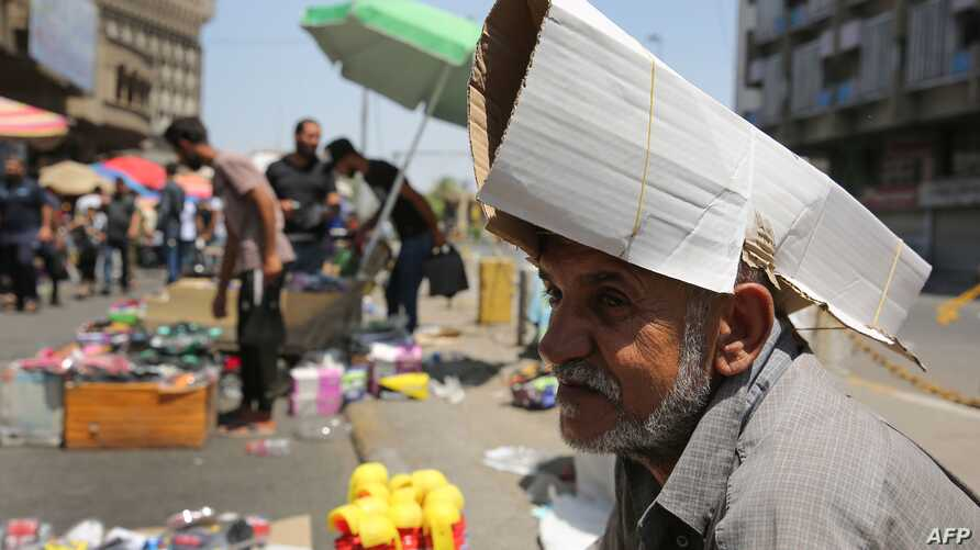 An Iraqi street vendor protects his head from the sun by using a piece of cardboard as a hat during a heat wave in the capital Baghdad, June 14, 2019.