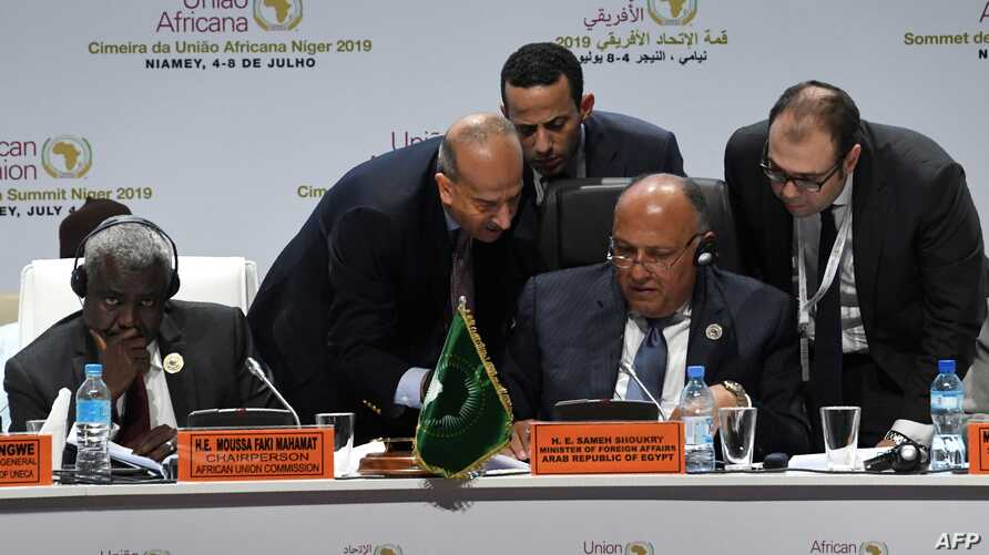 Egyptian Foreign Minister Sameh Shoukry (C) reads a document next to Chairperson of the African Union Commission Moussa Faki Mahamat (L) on the second day of the 35th Ordinary Session of the Executive Committee of the Meeting of the African Union at…
