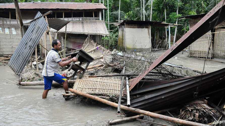 An Indian woman searches her belongings near the debris of her house following floodwaters in Kasuarbori village, in the Indias northeastern state of Assam, on July 13, 2019. At least 17 people have been killed across Nepal after torrential monsoon…