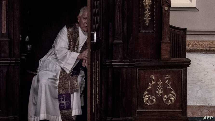 FILE - A priest hears a confession at the Metropolitan Cathedral in San Jose, Costa Rica on June 02, 2019.