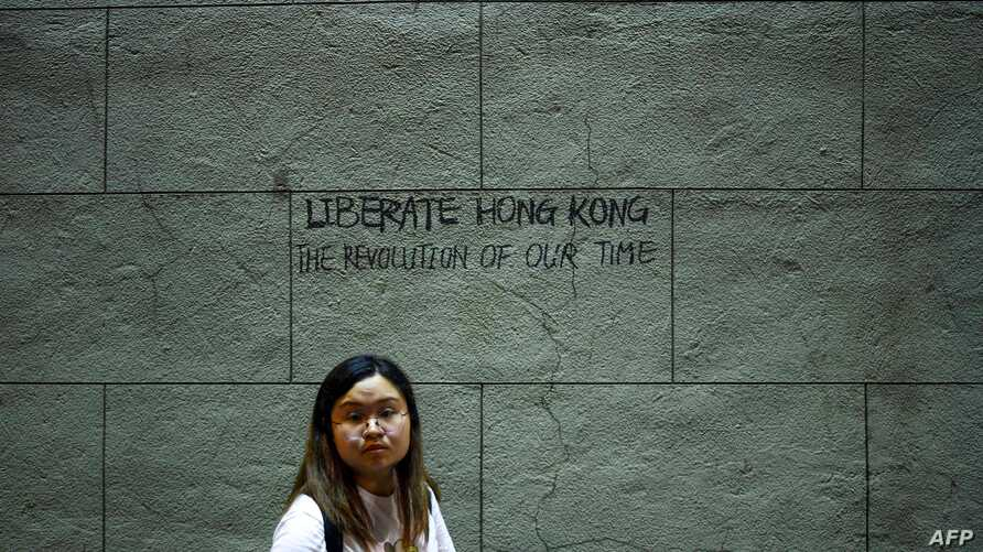 A pro-democracy protester walks past graffiti on a wall in Hong Kong, Aug. 16, 2019. Hong Kong's pro-democracy movement faces a major test this weekend as it tries to muster another huge crowd following criticism over a recent violent airport protest.