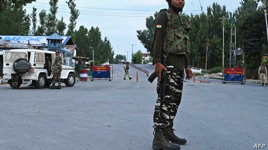FILE - Security personnel stand guard a street during a lockdown in Srinagar on Aug. 12, 2019.
