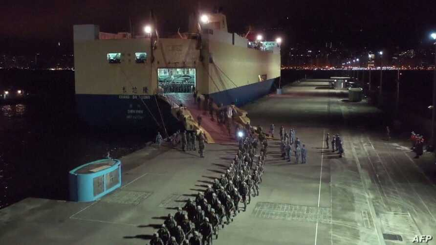 This screen grab taken from video released on August 29, 2019 from China's state-run CCTV shows People's Liberation Army (PLA) troops for the Hong Kong Garrison arriving on a ship in Hong Kong during a routine rotation of personnel. China's military…