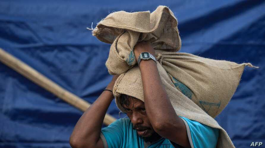 A Rohingya man carry relief aid at a camp in Teknaf on August 21, 2019. / AFP / MUNIR UZ ZAMAN