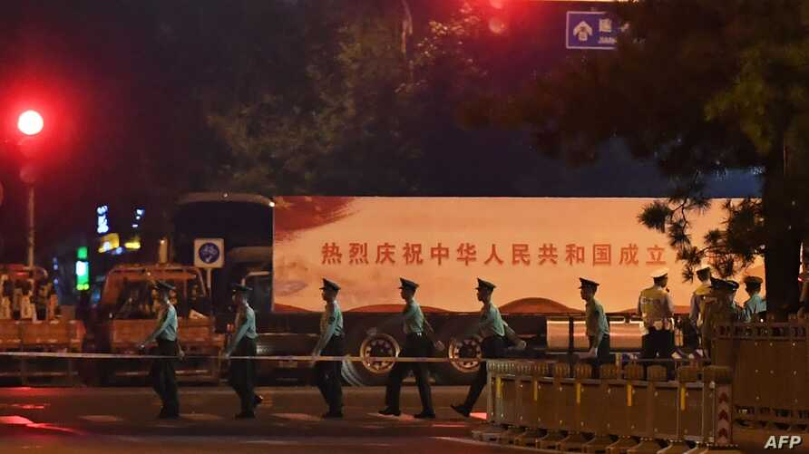 Paramilitary police march past trucks with propaganda slogans on Beijing's Changan Avenue, the city's main east-west boulevarde, during an overnight rehearsal of a military parade to mark Communist China's 70th anniversary, in Beijing on September 7…