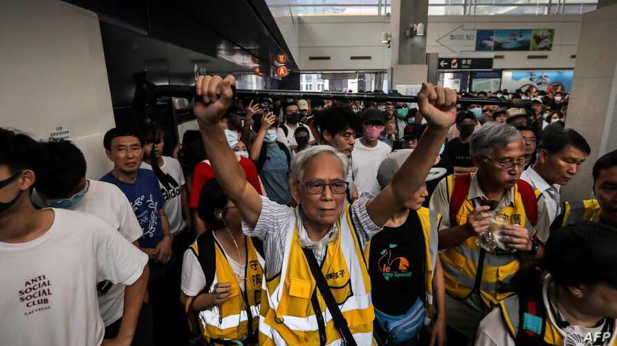 """This picture taken on September 7, 2019 shows """"Grandpa Wong"""" (C), 85, shielding protesters from the police by holding his walking stick up along with other """"silver hair"""" volunteers in the Tung Chung district in Hong Kong. Despite his age, Wong is a…"""