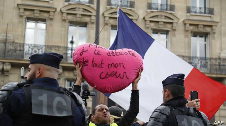"""A """"Yellow vest"""" protester holds a heart-shaped sign reading """"French President Emmanauel Macron I hate you with all my heart"""" in front of the Galeries Lafayette department store during an anti-government """"yellow vests"""" (gilets jaunes) protest in…"""