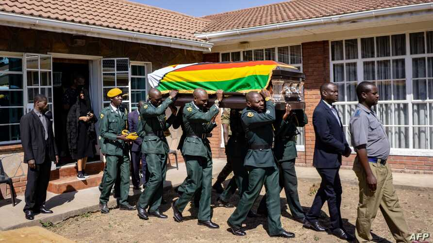 TOPSHOT - Pallbearers carry the coffin of late former Zimbabwe President Robert Mugabe for a mass at the family homestead in Kutama village, 80km northwest of Harare, on September 17, 2019. The remains of former Zimbabwe president Robert Mugabe, who…