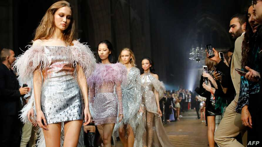 TOPSHOT - Models present creations from the 'Julien x Gabriela' collection by Julien Macdonald during a catwalk show for the Spring/Summer 2020 collection on the fourth day of London Fashion Week at Southwark Cathedral in London on September 16,…