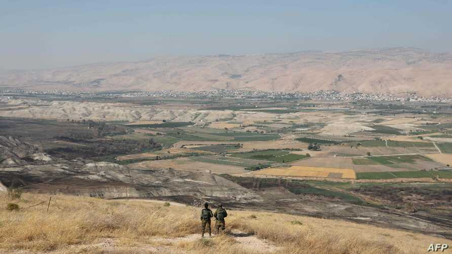 (FILES) In this file photo taken on June 23, 2019 Israeli soldiers stand guard in an old army outpost overlooking the Jordan Valley  between the Israeli city of Beit Shean and the West Bank city of Jericho. Israeli Prime Minister Benjamin Netanyahu…