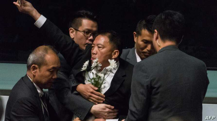 Pro-democracy lawmaker Wu Chi-wai (C) is escorted by security from the chamber after protesting as Hong Kong Chief Executive…