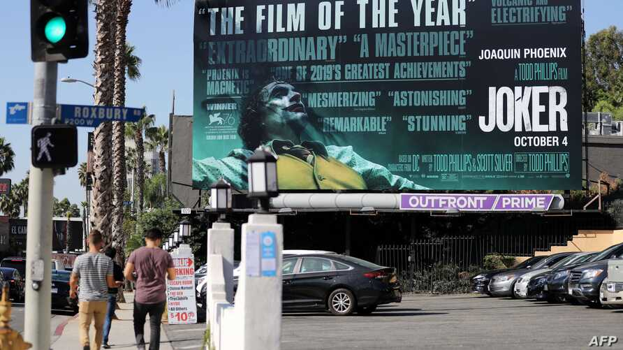 WEST HOLLYWOOD, CALIFORNIA - OCTOBER 03: People walk past a billboard displayed for the new film 'Joker' on October 3, 2019 in…