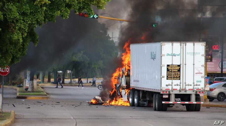 A truck burns in a street of Culiacan, state of Sinaloa, Mexico, on October 17, 2019. - Heavily armed gunmen in four-by-four…