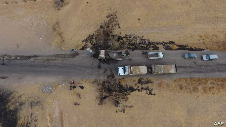An areal picture taken on October 28, 2019, shows vehicles near a destroyed truck at the spot where Abu Hassan al-Muhajir, the…