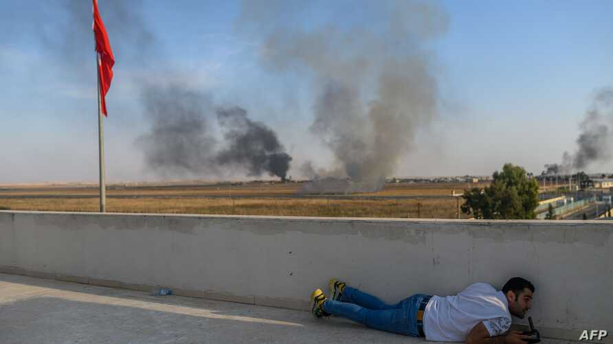 A journalist takes cover in Akcakale near the Turkish border with Syria on October 10, 2019 as a mortar landed nearby, on the…