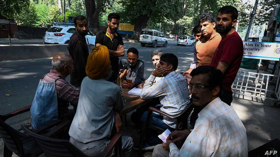 (FILES) In this file photo taken on September 3, 2019, people gather to make calls at a makeshift phone booth set up by Indian…