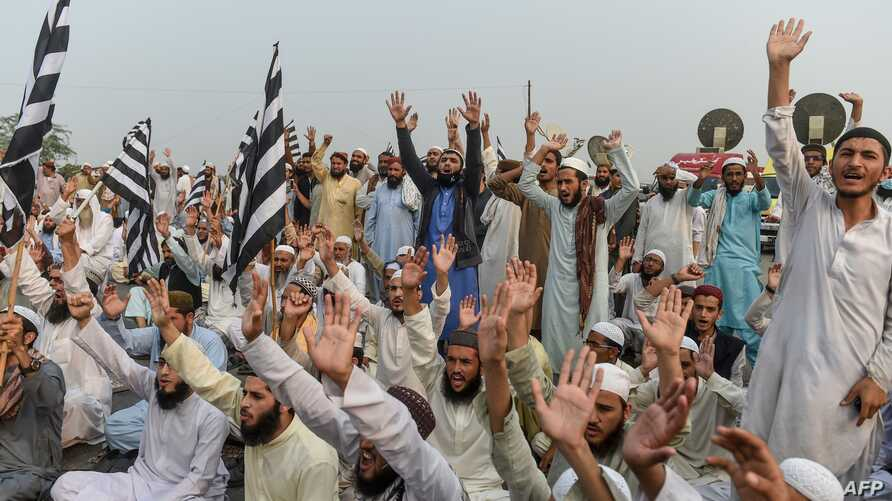Supporters of Islamic political party Jamiat Ulema-e-Islam (JUI-F) shout slogans as they block a highway during an anti…