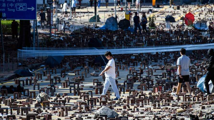 Pedestrians walk among bricks and debris left by protesters near the Hong Kong Polytechnic University in Hung Hom, Hong Kong on…