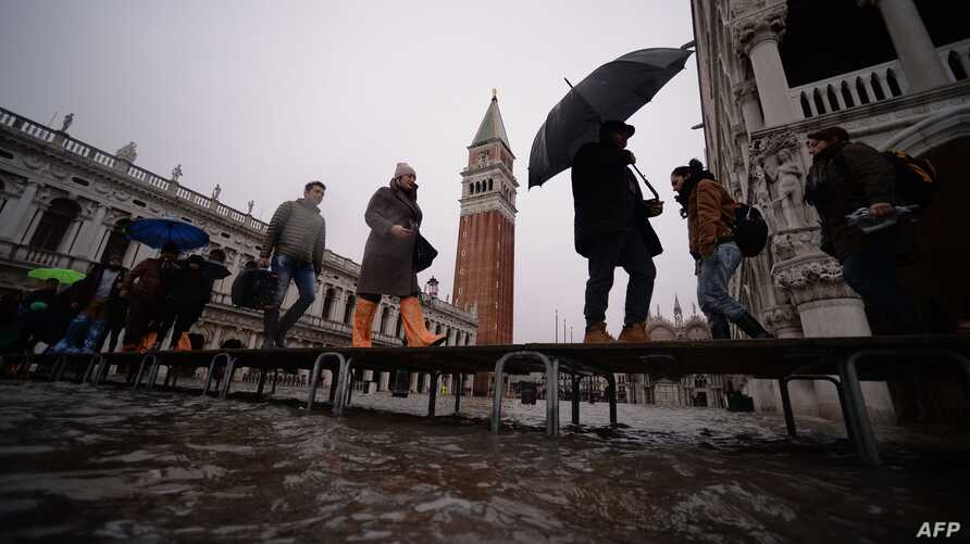 """Visitors walk in flooded St-Mark square in Venice, in the morning of November 17, 2019 prior an """"acqua alta"""", or high water, of…"""
