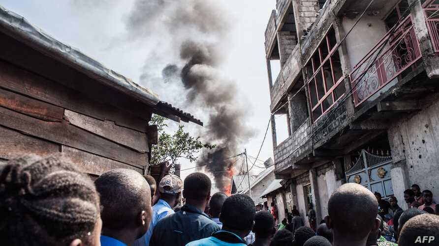 TOPSHOT - Residents react after a small aircraft crashed in a densely populated area in Goma on the East of the Democratic…