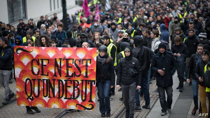"""Protesters hold a banner reading """"It's only the beginning"""" as they attend during a demonstration marking the first anniversary…"""