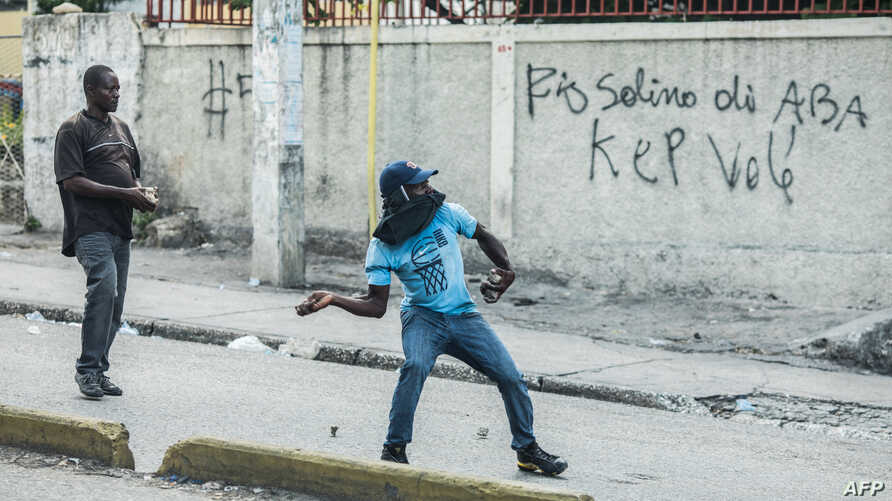 Protesters throw stones during an opposition demonstration commemorating the Battle of Vertieres Day, the last major battle of…