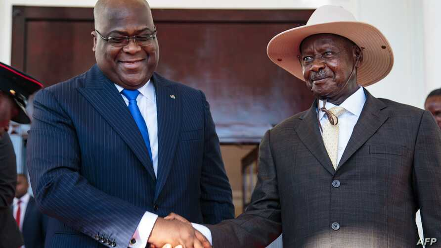 President of Democratic Republic of Congo (DRC) Felix Tshisekedi (L) shakes hands with Uganda's President Yoweri Museveni