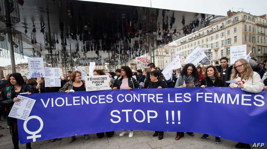 """Women hold a banner reading """"Stop violences against women"""" during a protest march to condemn violence against women, on…"""
