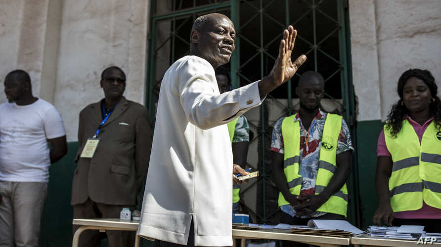 Guinea Bissau's president Jose Mario Vaz waves as he gets ready to cast his vote at a polling station in Bissau, on November 24…