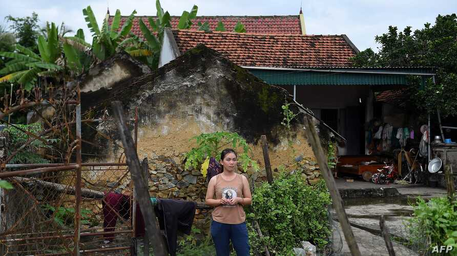 A Vietnamese woman  stands outside her house in Yen Thanh district of Vietnam's Nghe An province on October 27, 2019. - Dread…