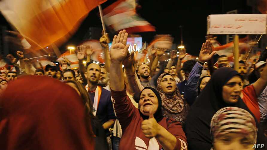 Lebanese protesters wave flags and shout slogans during an anti-government demonstration at al-Nour Square in the northern port…