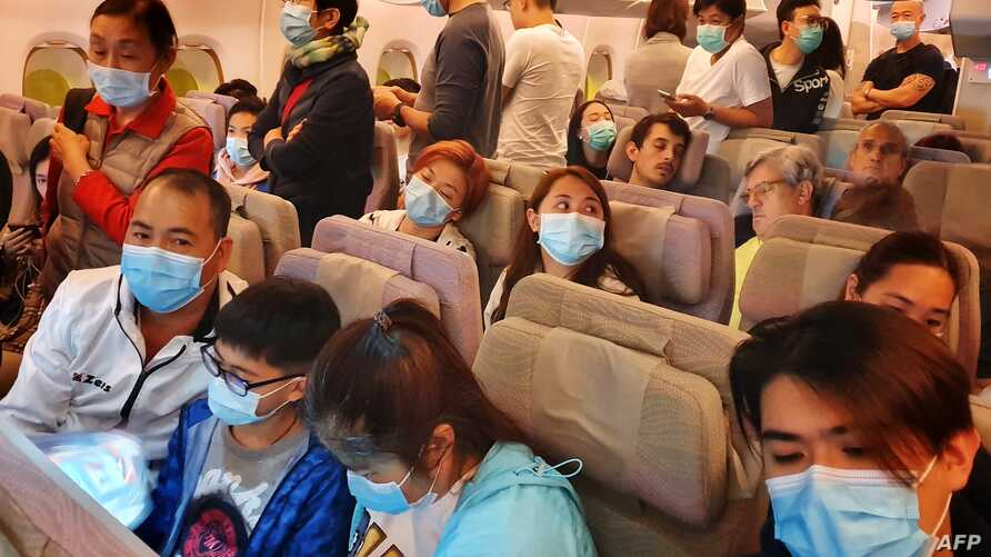 This picture taken on January 23, 2020 shows passengers wearing masks prepare to disembark from a flight from Hong Kong on…