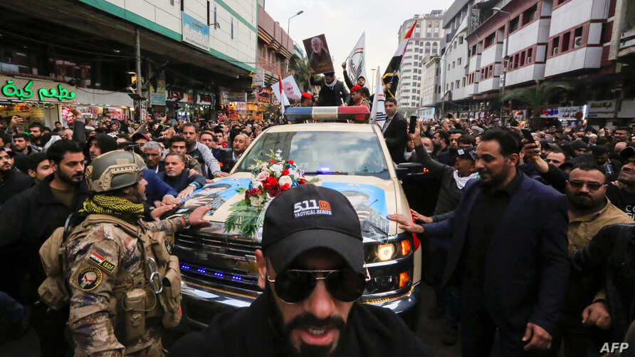 Mourners surround a car carrying the coffins of Iranian military commander Qasem Soleimani and Iraqi paramilitary chief Abu…