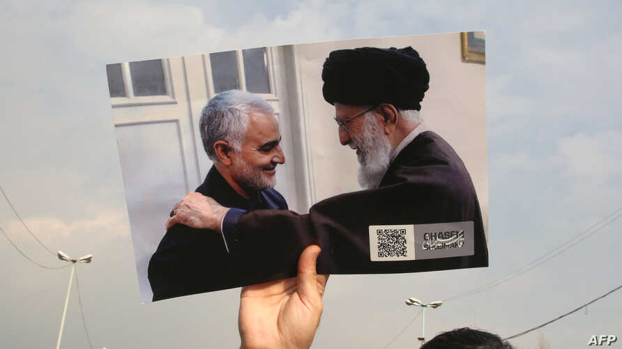A man holds a picture of Iran's supreme leader Ayatollah Ali Khamenei with Iranian Revolutionary Guards top commander Qasem…
