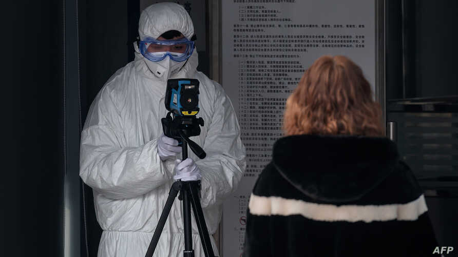 A security personnel wearing protective clothing to help stop the spread of a deadly virus which began in Wuhan, uses an…