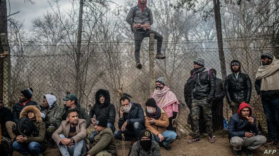 TOPSHOT - Migrants sit waiting near the buffer zone at Turkey-Greece border, at Pazarkule, in Edirne district, on February 29,…