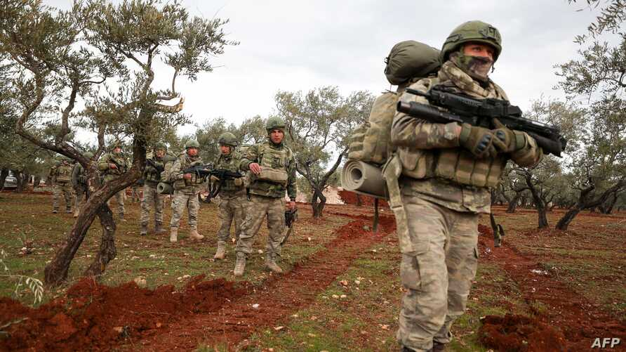Turkish soldiers gather in the village of Qaminas, about 6 kilometres southeast of Idlib city in northwestern Syria on February…