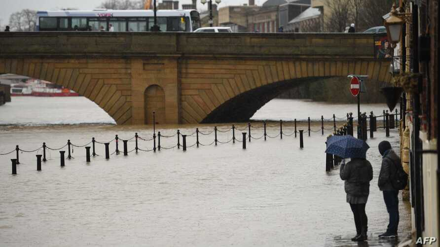 Pedestrians walk on the Ouse Bridge as the level of the River Ouse rises in York, North Yorkshire on February 15, 2020, as…