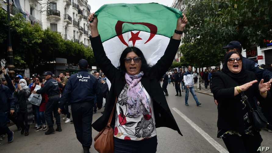 TOPSHOT - An Algerian woman waves a national flag as she takes part in an anti-government demonstration in the capital Algiers…
