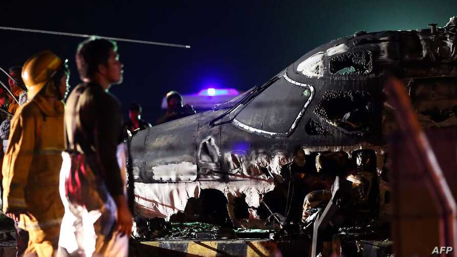 Rescuers stand next to the wreckage of a Westwind aircraft after it caught on fire during takeoff at Manila international…