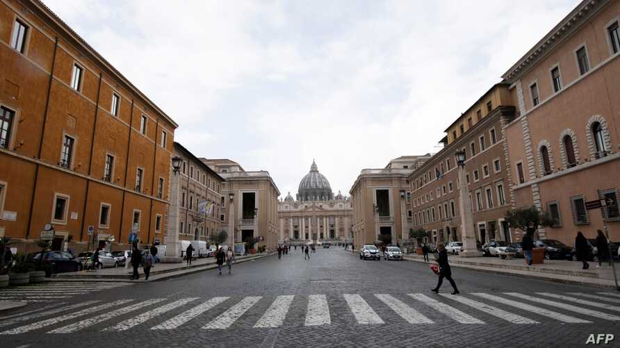 Tourists walk near St. Peter's square at the Vatican,  on March 3, 2020.